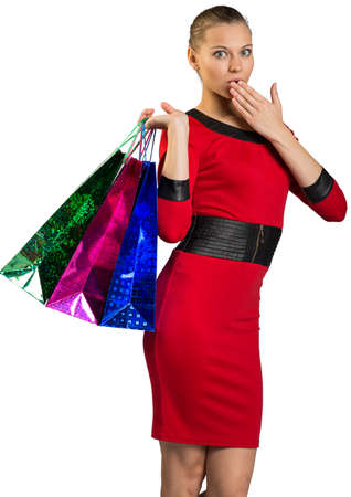 half turn: Half-turned young woman covering mouth and handing colorful shopping bags, looking at camera. Isolated background Stock Photo