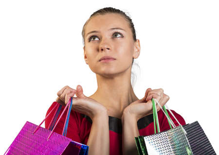 looking in corner: Sad young lady handing colorful shopping bags and looking upper left corner. Closed up. Isolated background Stock Photo