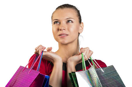 looking in corner: Sad young lady handing colorful shopping bags, narrowing her eyes and looking upper left corner. Closed up. Isolated background