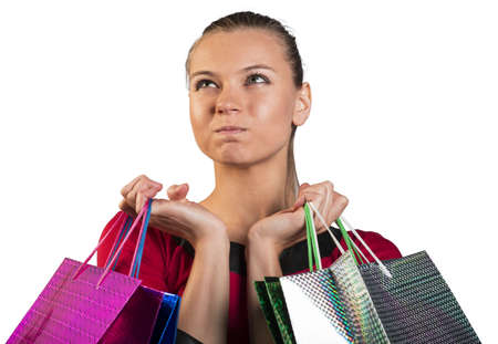 looking in corner: Angry young lady handing colorful shopping bags, narrowing her eyes and looking upper left corner. Closed up. Isolated background