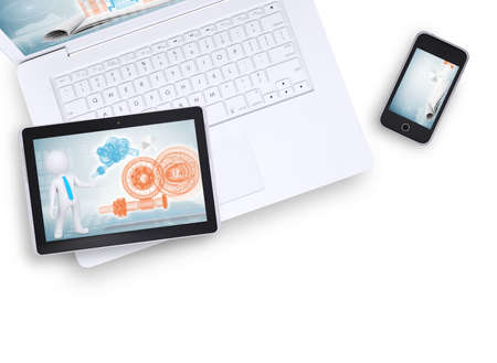 Tablet on laptop and mobile phone near on isolated white background, top view. Closed up photo