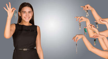 alright: Smiling business woman with house keys and several hands offering keys looking at camera. Isolated grey background Stock Photo