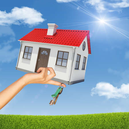 close up chimney: House and keys in womans hand on nature background with blue sky Stock Photo