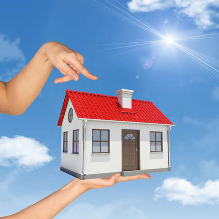 fingering: Womans hand fingering at house on palm, blue sky background