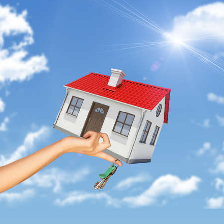close up chimney: House and keys in womans hand on blue sky background