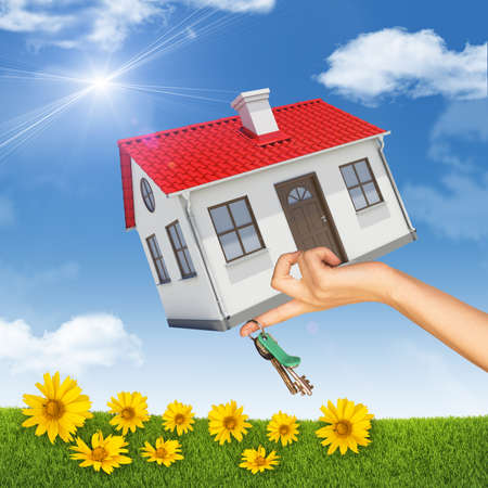 close up chimney: House and bunch of keys in womans hand on nature background with blue sky and yellow flowers