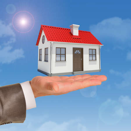 close up chimney: House under businessmans hand on blue sky background Stock Photo