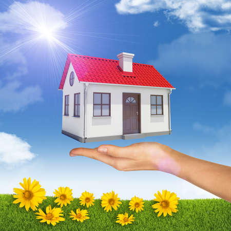 close up chimney: House under businesswomans hand on nature background