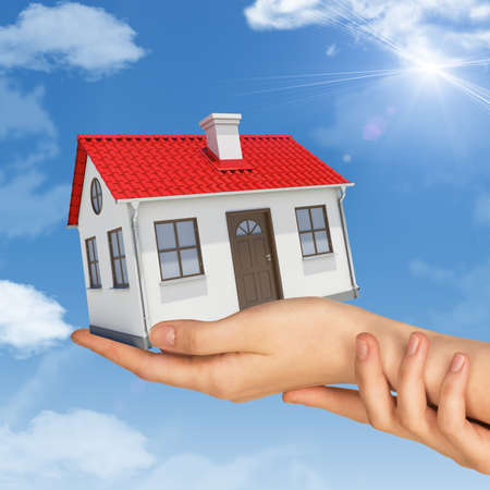 close up chimney: Womans hands holding house on blue sky background