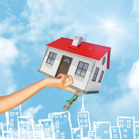 close up chimney: House and bunch of keys in businesswomans hand on sky background and city drawn in pencil Stock Photo