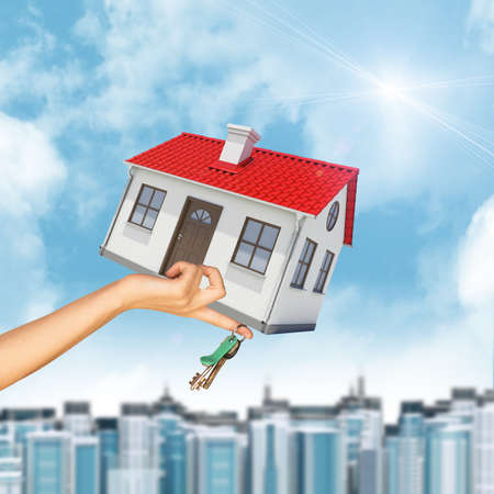 close up chimney: House in businesswomans hand with cityscape on blue sky background