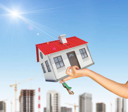 close up chimney: House in businesswomans left hand with cityscape on blue sky background