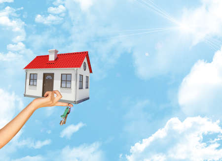 close up chimney: House and keys in businesswomans hand on blue sky background with bright sun Stock Photo