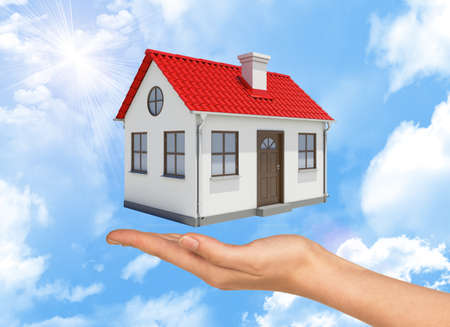 close up chimney: House under businesswomans hand on cloudy blue sky background