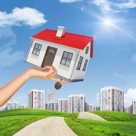 close up chimney: House and keys in womans hand on cityscape background with blue sky