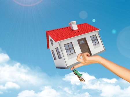 close up chimney: House and keys in womans left hand under clouds on blue sky background