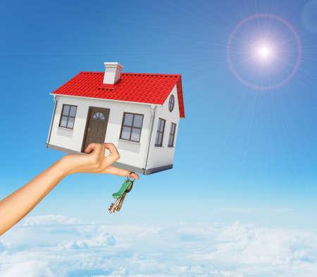 mano derecha: Casa y claves en la mujer la mano derecha bajo las nubes sobre fondo azul cielo Foto de archivo