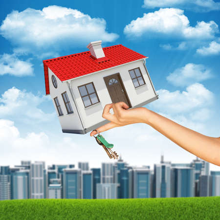 close up chimney: House and keys in businesswomans hand on cityscape background with cloudy blue sky