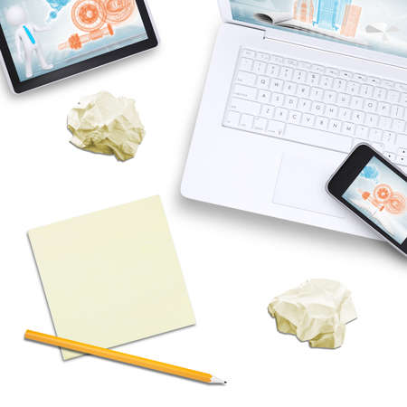 Mobile phone on laptop with tablet, note paper on isolated white background, top view photo