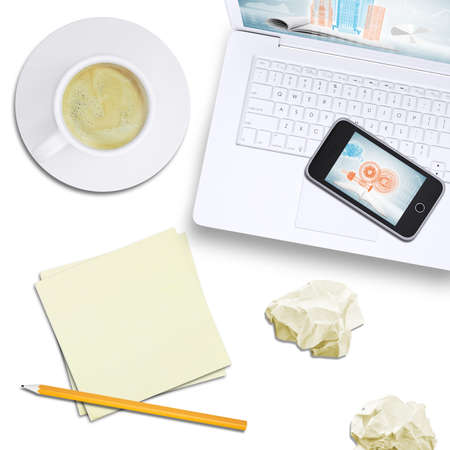 Mobile phone on laptop with tablet, note paper and coffee on isolated white background, top view photo