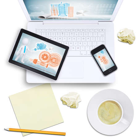 Tablet and mobile phone on laptop with coffee cup, crumpled paper on isolated white background, top view photo