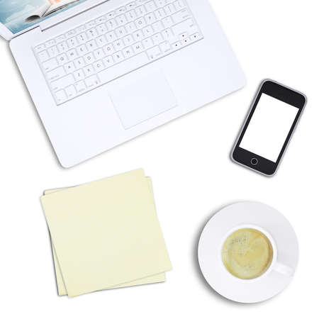 White laptop with mobile phone and coffee cup on isolated white background, top view. Closed up photo