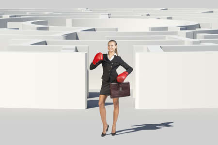 Businesswoman in boxer gloves shouting and looking at camera, near labyrinth, closed view. Isolated background, virtual model photo