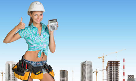 Smiling young woman in hard hat holding calculator and looking at camera on construction and building cranes background