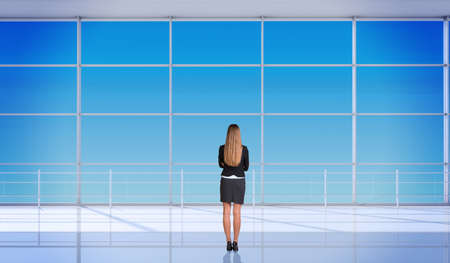 backview: Young businesslady with crossed arms and standing back in front of window. Interior view Stock Photo