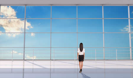 backview: Businesslady standing back in front of window, blue sky background. Interior view