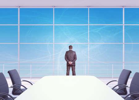 out of office: Businessman looking out office window, rear view. Blue sky background