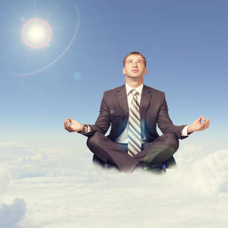 Businessman sitting in lotus position on cloud and looking up photo