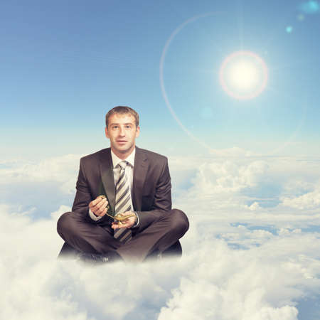 Businessman sitting in lotus position on cloud, holding oil lamp and looking at camera photo