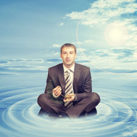 lotus position: Businessman sitting in lotus position on cloud with oil lamp and looking at camera