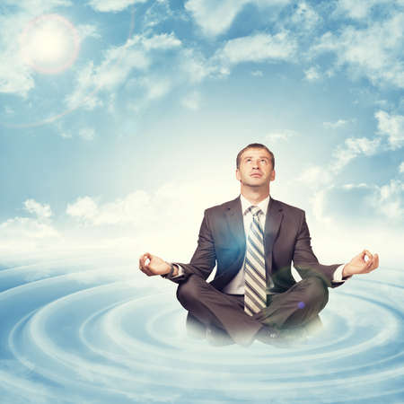 lotus position: Businessman sitting in lotus position on cloud with circles and looking up