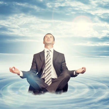 Businessman sitting in lotus position on cloud with circles and looking up on blue sky background photo