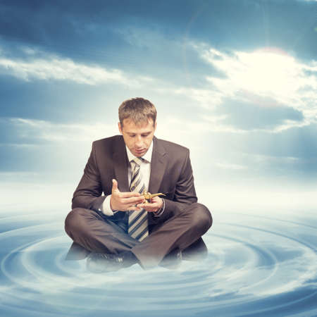 Businessman in suit sitting in lotus position on cloud with circles and looking at oil lamp on blue sky background photo