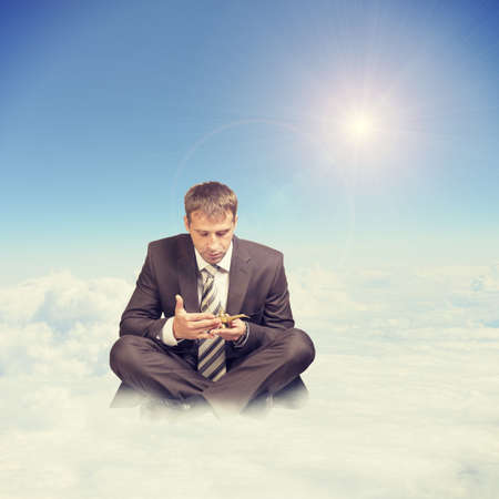 Businessman in suit sitting in lotus position on cloud and looking at oil lamp on blue sky background photo