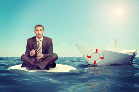 lotus position: Businessman sitting in lotus position with paper boat in sea and looking at camera