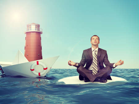 lotus position: Businessman sitting in lotus position with paper boat and lighthouse in sea and looking at camera