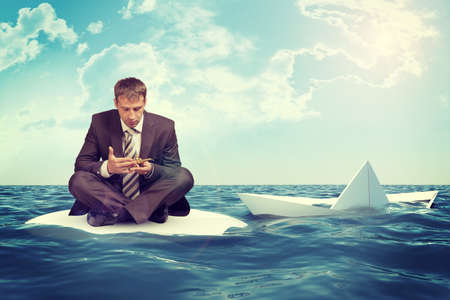 lotus position: Businessman sitting in lotus position on small sand island in sea and looking up, sinking paper boat on right side Stock Photo