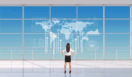 Businesswoman with hands on waist in front of window, back view. Interior view photo