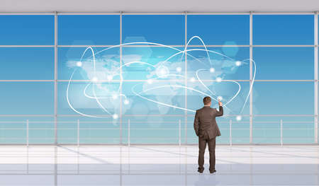 Businessman touching holographic screen in front of window, back view. Interior view photo