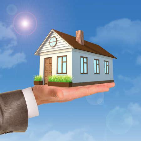 mano derecha: Casa en businessmans mano derecha sobre fondo azul cielo