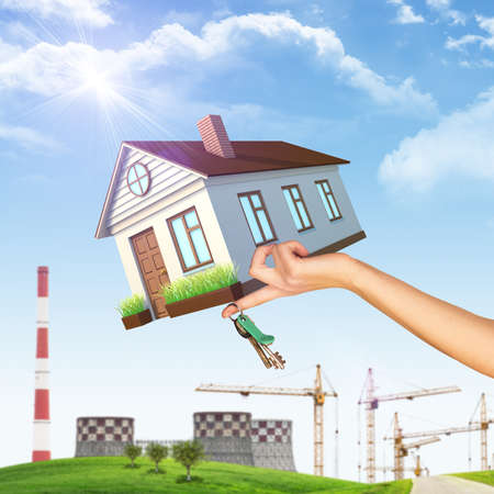 House on businesswomans hand on nature background with building crane, NPP