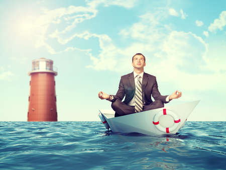 lotus position: Businessman sitting in lotus position on paper boat and lighthouse in sea and looking up