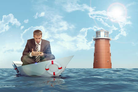 lotus position: Businessman sitting in lotus position in paper boat in sea and looking at oil lamp Stock Photo