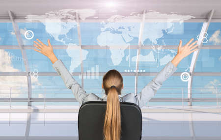 arm chairs: Rear view of businesswoman sitting in chair with arms up in front of window with virtual world map
