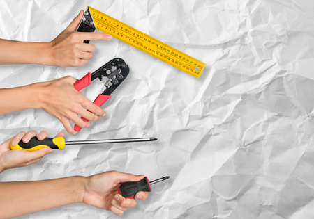 upkeep: Peoples hands holding different tools on crumpled paper background Stock Photo