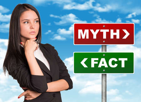 fact: Thoughtful businesswoman standing near colorful myth and fact signboards and looking right side on blue sky background Stock Photo
